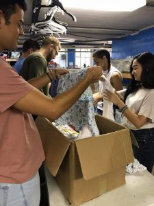 Students from local colleges help sort clothes for the Downtown food and clothing bank.
