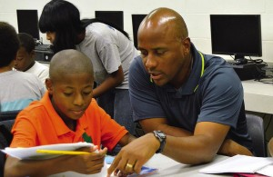 MaliVai Washington assists student with homework in the Tennis & Tutoring (TnT) program. Students in the program