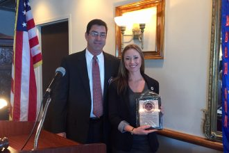 President George Mann, left, and The Exchange Club of Jacksonville honored Megan Zimmerly with its Random Act of Kindness Award on Oct. 26, in recognition of her exceptional display of community service for her efforts in rescuing a woman who had jumped into the St. Johns River. Community service and Americanism are at the cornerstone of the organization's programs of service.