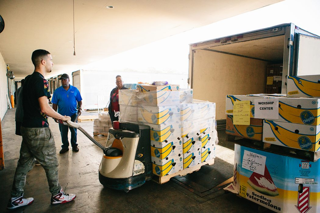Feeding Northeast Florida warehouse worker Cosme Corona loads items into a partner agency's truck.
