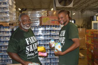 Karey Gee and Alex Hagans sort food at the Farm Share warehouse on Jessie Street in Jacksonville.