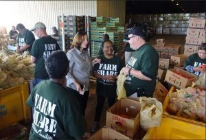Emma Holt (middle) joins other Farm Share volunteers at the warehouse on Jessie Street in Jacksonville.