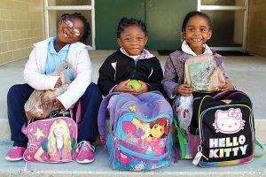 Three little girls are happy to receive backpacks filled with food and supplies from Lutheran Social Services.