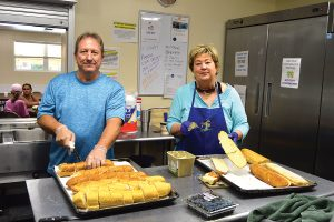Gary Fregeau and his wife, Karen, of Our Lady Star of the Sea Catholic Church, prepare bread for lunch at Mission House.