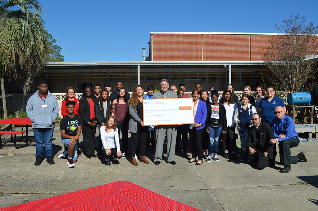"Big Brothers Big Sisters CEO Sara Alford, Hyatt Regency Jacksonville Riverfront General Manager Luis Aloma, and Carolyn Shuck, Hyatt's director of human resources hold a check for $12,000, which he presented to Big Brothers Big Sisters of Northeast Florida Dec. 4 at Terry Parker High School. Included in the photo are ""Bigs and Littles,"" students who are part of the nonprofit's Beyond School Walls program."
