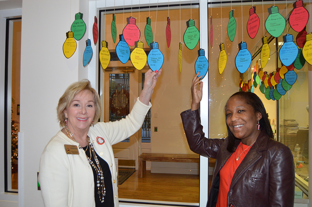 Development Director Carol Harrison and Marketing Director Ashley Strickland with the pledge light bulbs that are hanging in the lobby of the house.