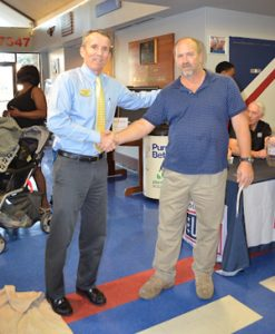 Greater USO Executive Director Mike O'Brien (left) shakes hands with Subway representative Fred Gardner (right) at the Greater Jacksonville USO office during a No Dough Dinner event.