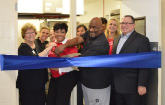 Cutting the ribbon to unveil the new Wells Fargo Community Kitchen were Penny Kievet, executive director of the City Rescue Mission; Cheryl Clark, City Rescue Mission chef; Heather Fincher, Valerie Jenkins, and Monica Smolder of Wells Fargo; CRM Chef Ron Scott; Keri Michelle Shaw and Michelle Berman of Wells Fargo; Mark Middlebrook, regional manager, north and central Florida for Wells Fargo Investment and Fiduciary Services
