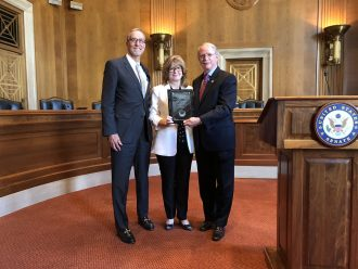 AHTCC President Michael Gaber looks on as Sulzbacher President and CEO Cindy Funkhouser receives the Charles L. Edson Tax Credit Award from Rep. John Rutherford.