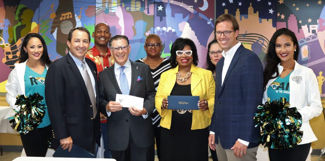Flanked by members of the Jaguars ROAR are Chris Sutton, Joe Whitaker, Ju'Coby Pittman and Michael Pajcic. In back: Thomas Waters, Diana Mason, and Dee Paez, board members.
