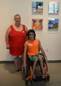 Raven and his mother in front of his art at the annual Art With a Heart in Healthcare exhibit at MOCA.