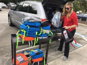 Amy Vincent, from LandSouth, unloads backpacks to donate to Youth Crisis Center students.