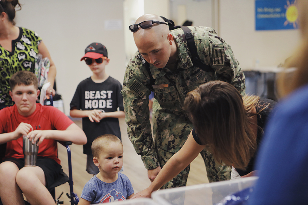 A military father helps his preschool-age son select school supplies, courtesy of Operation Homefront.